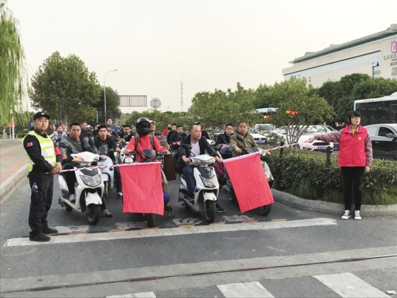 新式小红旗亮相文明交通示范路口 旗杆加长 可对非机动车进行有效管理